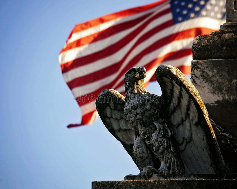 Eagle Statue in front of United State flag. The United States flag blows in the wind behind a weathered statue of a an American Eagle framed by a bright blue sky royalty free stock image