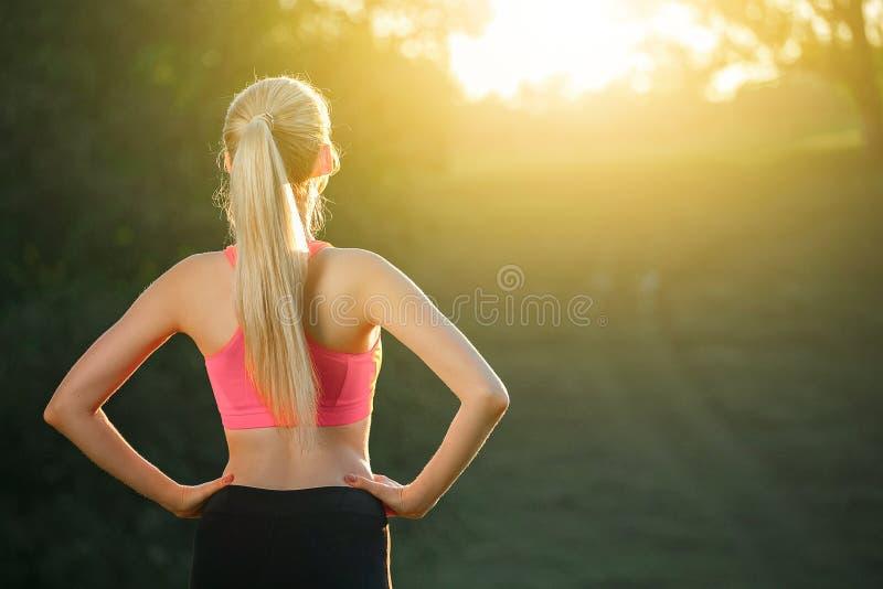 Ealthy炫耀生活方式 体育的运动少妇穿戴做健身锻炼 有吸引力的照相机特写镜头健身增强的微笑衡量妇女 免版税库存图片