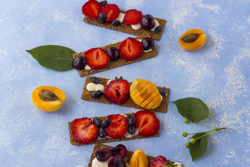 Ealthy and tasty toasts with curd cheese, fruits and berries on a blue background stock image