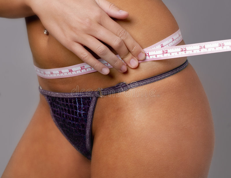 Ealthy woman measuring her waistline royalty free stock image