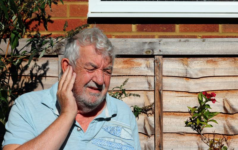 Ear ache or pain. Senior man holding his ear because of pain or ear ache royalty free stock image