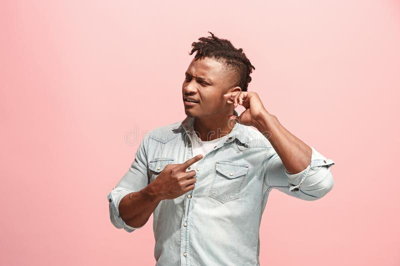 The Ear ache. The sad Faro-American man with headache or pain on a pink studio background. Sore ear. Ear ache concept. The sad afro man with Ear ache or pain on royalty free stock photos