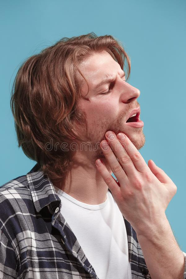 The Ear ache. The sad man with headache or pain on a blue studio background. Sore ear. Ear ache concept. The sad crying man with headache or pain on trendy blue royalty free stock image