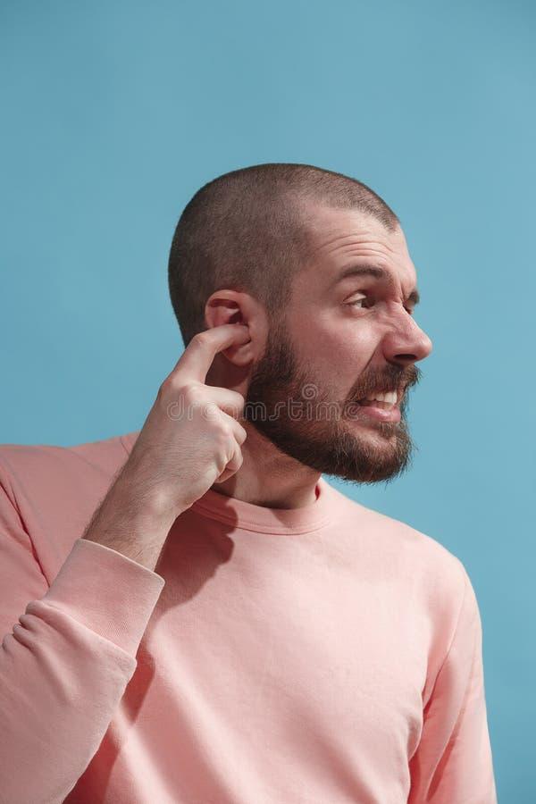 The Ear ache. The sad man with headache or pain on a blue studio background. Sore ear. Ear ache concept. The sad crying man with headache or pain on trendy blue stock image