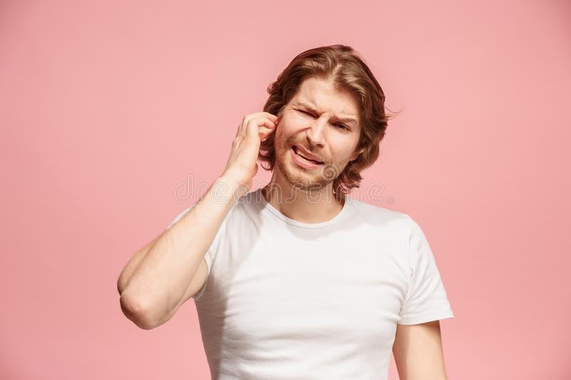The Ear ache. The sad man with headache or pain on a pink studio background. Sore ear. Ear ache concept. The sad crying man with headache or pain on trendy pink royalty free stock photo