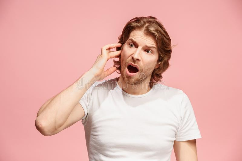 The Ear ache. The sad man with headache or pain on a pink studio background. Sore ear. Ear ache concept. The sad crying man with headache or pain on trendy pink stock photos
