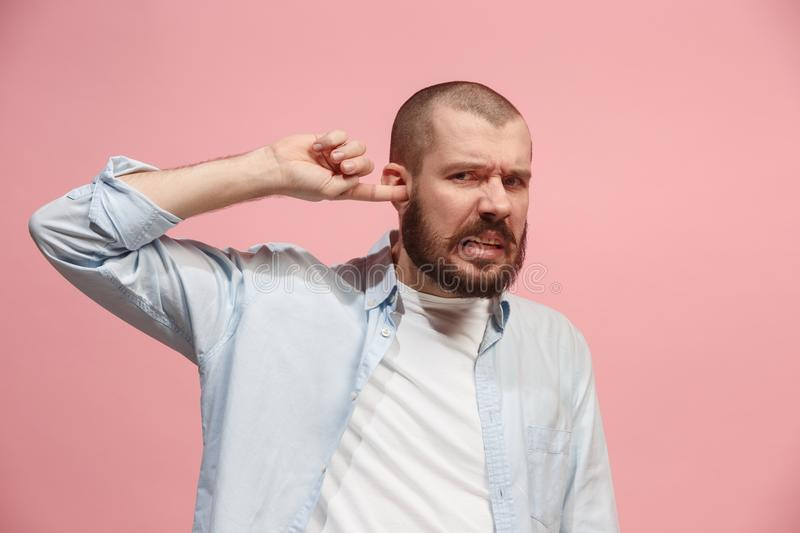 The Ear ache. The sad man with headache or pain on a pink studio background. Sore ear. Ear ache concept. The sad crying man with headache or pain on trendy pink royalty free stock image