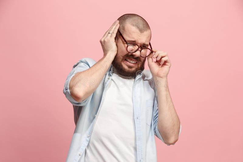 The Ear ache. The sad man with headache or pain on a pink studio background. Sore ear. Ear ache concept. The sad crying man with headache or pain on trendy pink royalty free stock photos