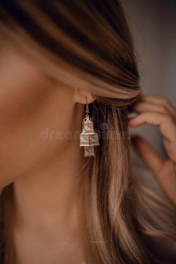 Ear with a beautiful birds earring. Ear with a beautiful stylish birds earring royalty free stock images