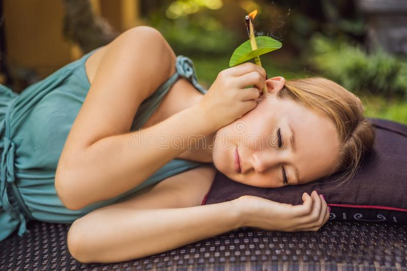 Ear candling being carried out on an attractive caucasian woman in a spa.  stock images