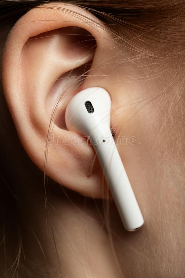 Ear with earphone. Female ear with bluetooth earphone closeup view stock images