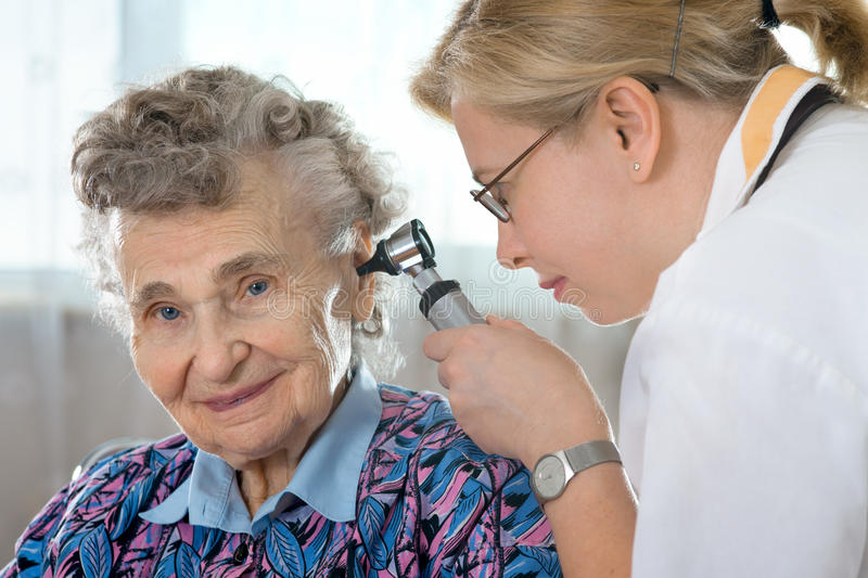 Ear exam. Doctor performing ear exam with otoscope royalty free stock images