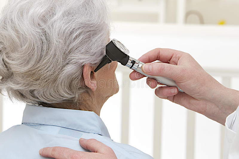Ear exam for senior woman. Back view of Doctor performing ear exam with otoscope on a senior patient stock photography
