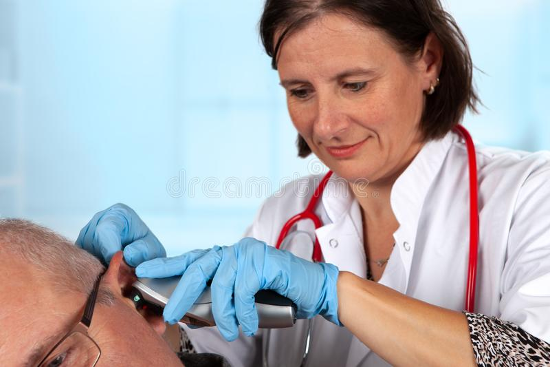 Ear examination by a doctor with otoscope. royalty free stock photo