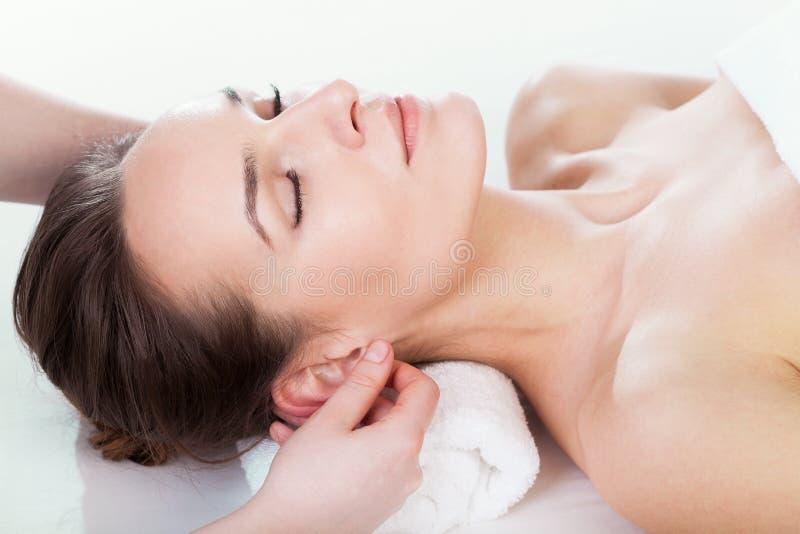 Ear massage. Woman enjoying ear massage at beauty salon