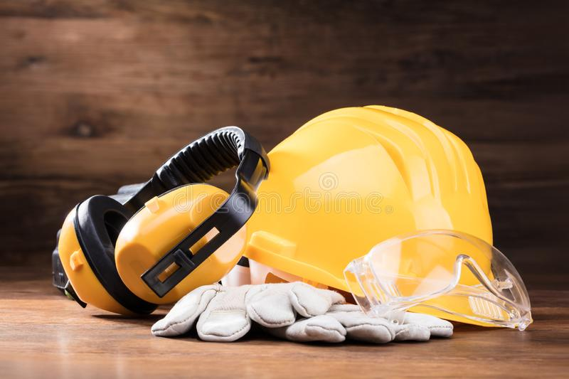 Ear Muff, Safety Glasses, And White Gloves On Table stock photography