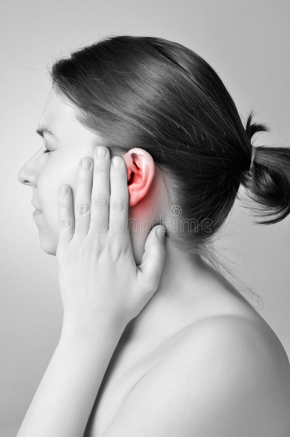 Ear pain. Young woman touching her painful ear stock photography