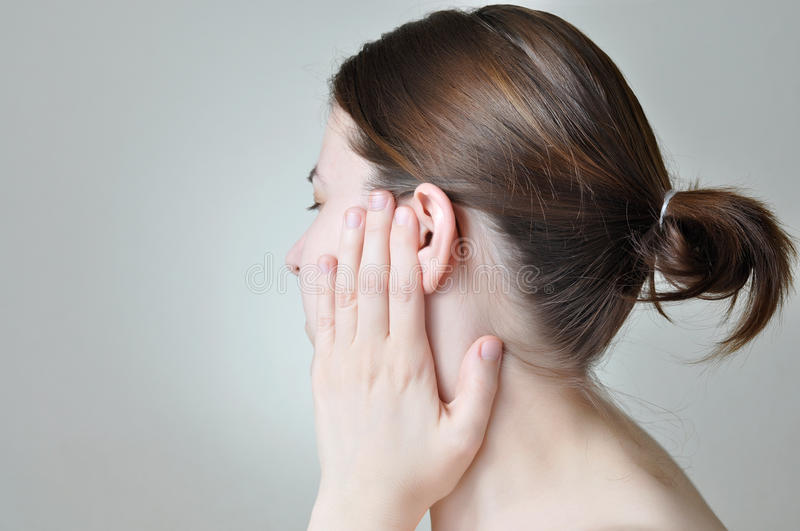 Ear pain. Young woman touching her painful ear stock images