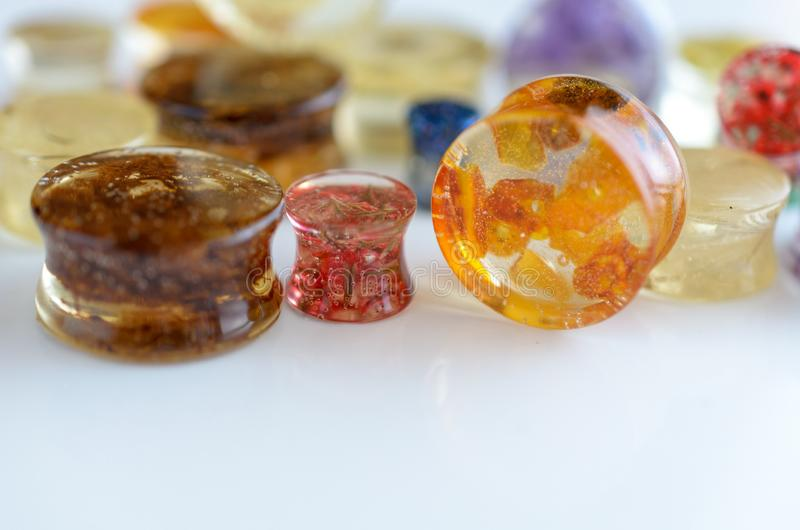 Ear piercing plugs, tunnels, gauges of epoxy resin close-up royalty free stock image