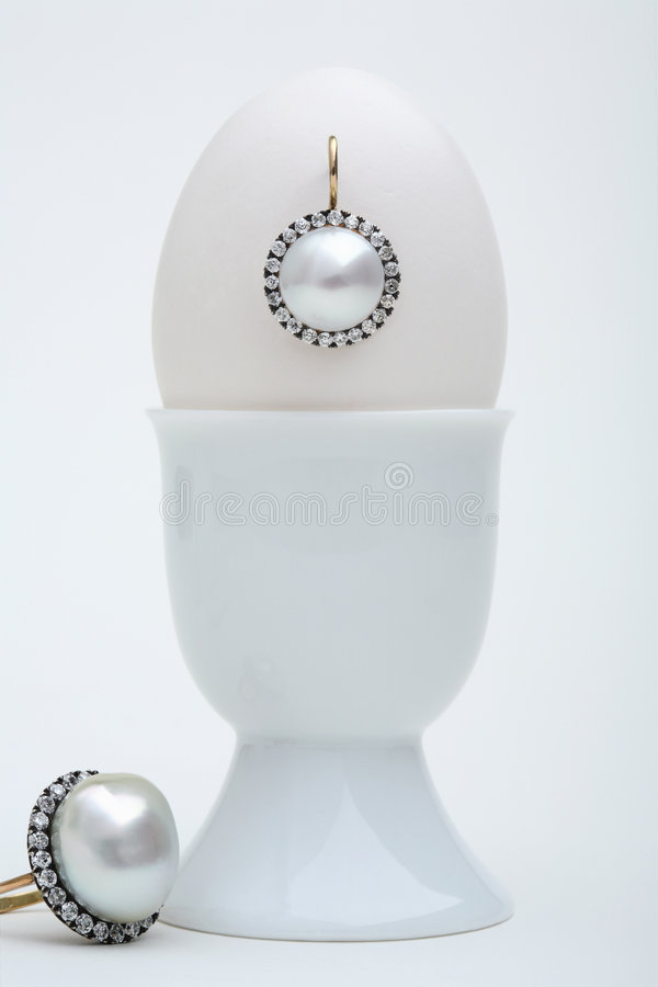 Ear-ring. Still-life with diamond ear-ring and egg stock photos