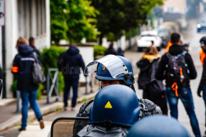 Ear view of police officers looking at journalists yellow vests protest. Strasbourg, France - Apr 28, 2019: Rear view of French police officers looking at royalty free stock photos