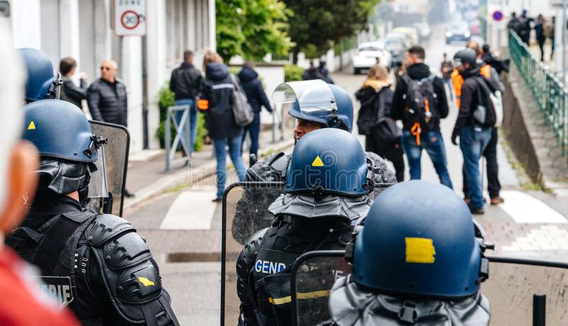Ear view of police officers looking at journalists yellow vests protest. Strasbourg, France - Apr 28, 2019: Rear view of police officers looking at journalists royalty free stock photos