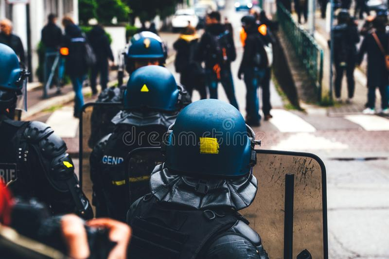 Ear view of police officers looking at journalists yellow vests protest. Strasbourg, France - Apr 28, 2019: Rear view of police officers looking at journalists royalty free stock image