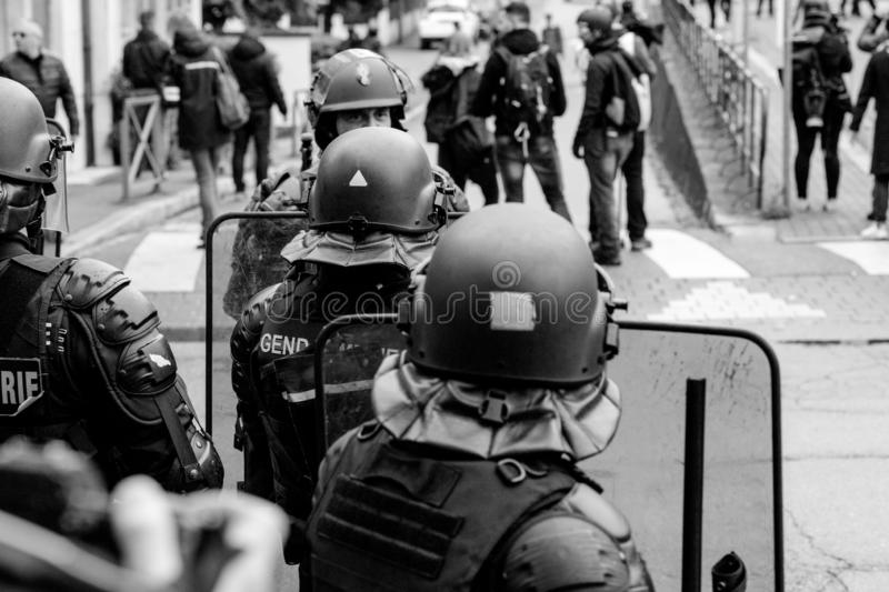 Ear view of police officers looking at journalists yellow vests protest. Strasbourg, France - Apr 28, 2019: Rear view of police officers looking at journalists royalty free stock photography