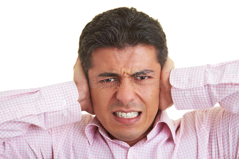 Earache. Man covering his ears with his hands stock photography