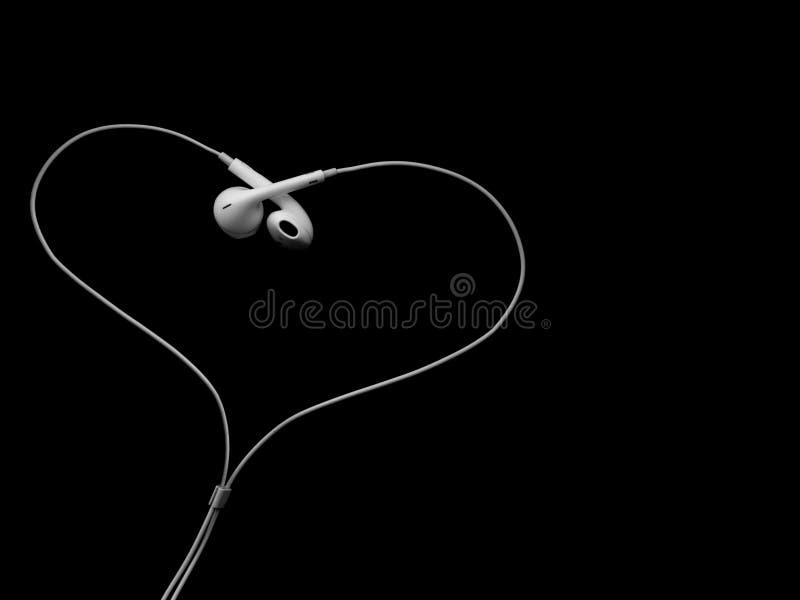 Earbuds de câble blancs d'écouteurs, casque sous forme de coeur sur un fond noir images stock