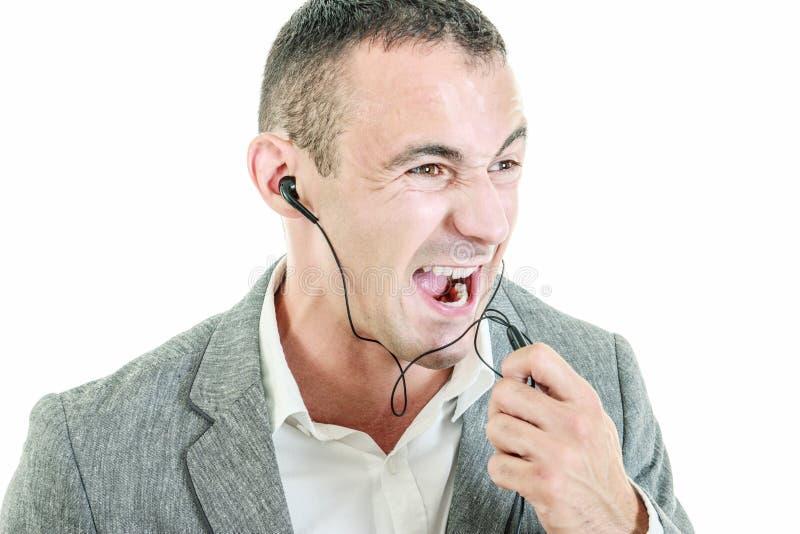 Earbuds vestindo do homem que falam na gritaria do telefone celular imagem de stock royalty free