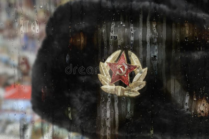 Earflaps fur cap with  red star in a souvenir shop in Russia. Rainy day stock images