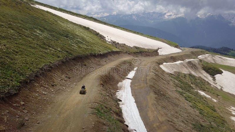 在他的途中的方形字体自行车高在山顶部 免版税图库摄影
