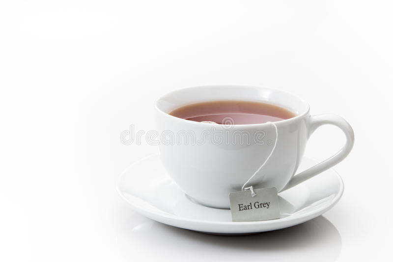 Earl Grey tea in a white cup on a saucer on a white background stock image