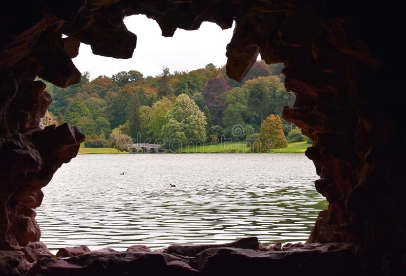 An early Autumn / Fall scene through the stone window of a rustic garden grotto stock photo