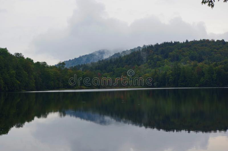 Early Autumn foliage on a misty Lake in the Adirondack Mountains of Upstate New York. A very misty day royalty free stock photos