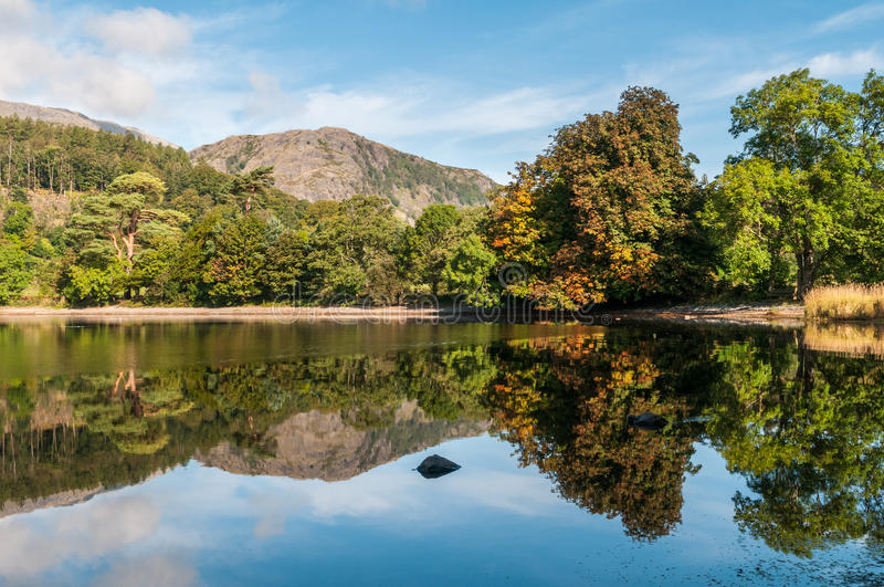 Early autumn reflections at Coniston Water. An early autumn view of Coniston Water in the English Lake District. The first leaves of the trees are starting to royalty free stock images