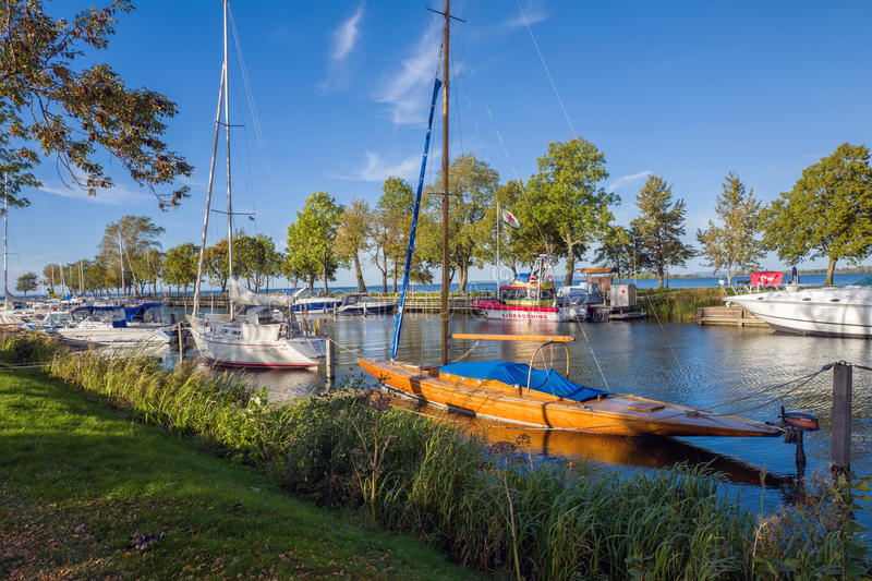 Early autumn in Vadstena. Vadstena, Sweden – September 30, 2015: Leisure boats moored at the harbor in Vadstena during early autumn. Vadstena is a stock photography