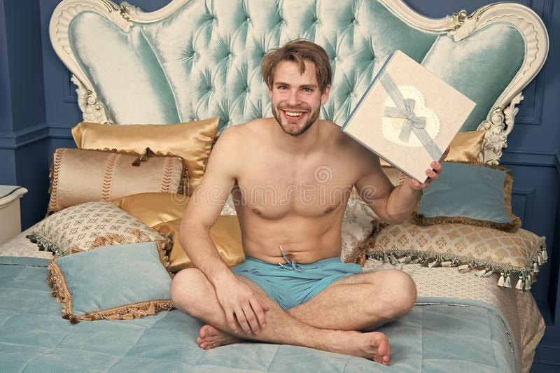 An early birthday present. Sexy man smiling with birthday gift in bed. Happy man holding birthday present wrapped in box. An early birthday present. Sexy man royalty free stock photography