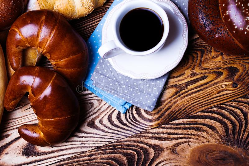 Early breakfast. Cup of coffee on a saucer with bakery products on a wooden table royalty free stock images