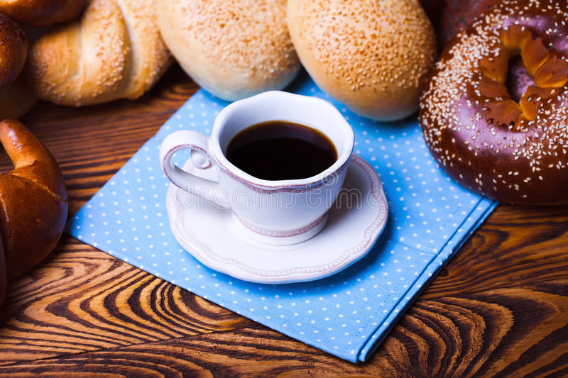 Early breakfast. Cup of coffee on a saucer with bakery products on a wooden table stock photography
