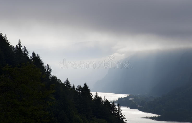 Early Dawn In The Columbia River Gorge. Moody skies in this picture of storm clouds filtering the morning sun rays on a cold wet day in the Columbia River Gorge stock images