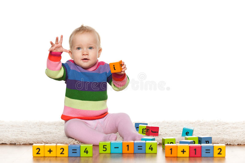 Early learning of a baby girl. A baby girl is playing with blocks with digits on the floor stock photos