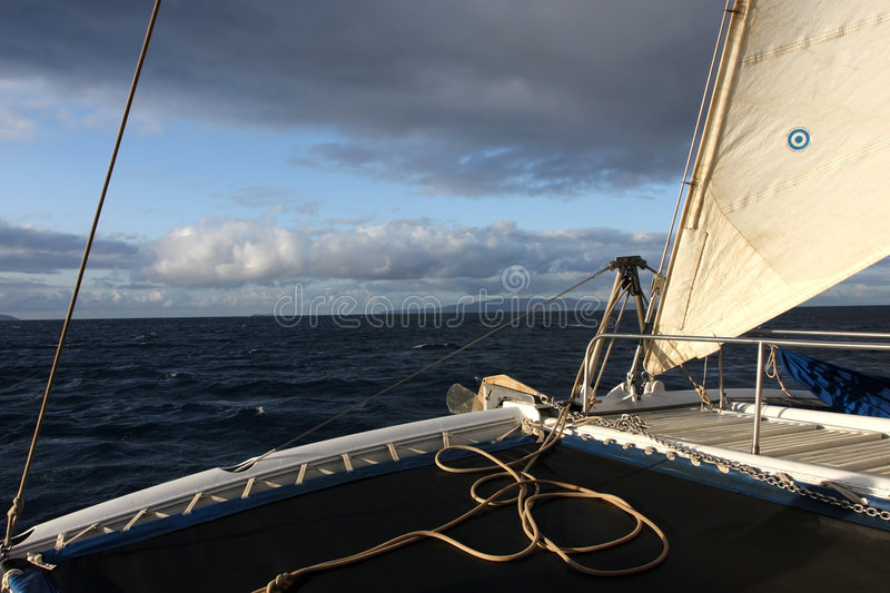 Early Morning Adventure. The jib sail being filled with air on a catamaran as the sun starts to break through the clouds royalty free stock images