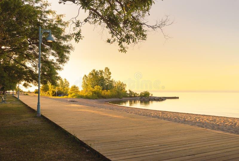 Early morning along a lakeside beach boardwalk stock image