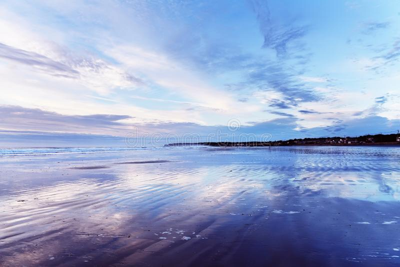 Early  morning on the Atlantic coast. Reflection of the dawn sky in the water on the sand. USA. Maine. royalty free stock photos