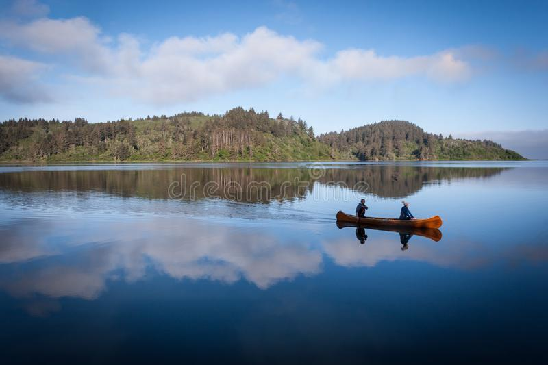 Early Morning Canoe Ride. A couple glides across a calm lagoon in the Humboldt National Lagoons State Park in California on an early morning, reflected in the royalty free stock images