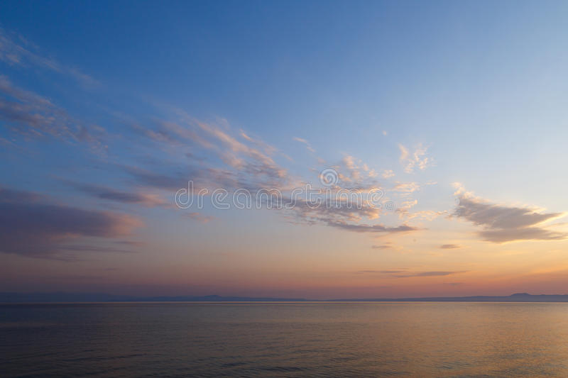 Early morning at dawn of the day with a calm blue sea overlooking the cloudy sky and mountains of the other shore stock photography