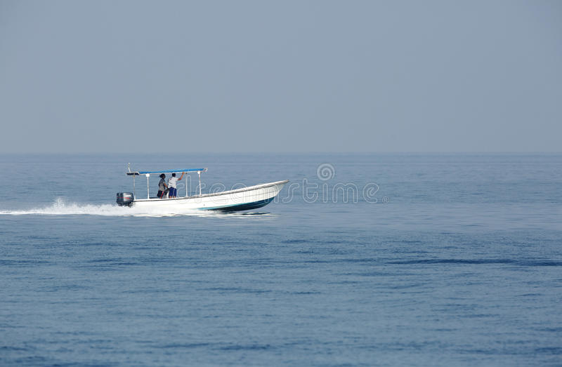 Early morning fisher men moving in sea on speedboat royalty free stock image
