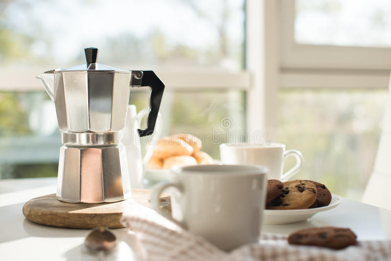 Early morning french home breakfast with coffee. Early morning french home breakfast, coffee and cookies on the table near window in bright sunlight, white stock image